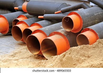 The process of laying of utilities. A pile of black pipe with an orange base in sand.