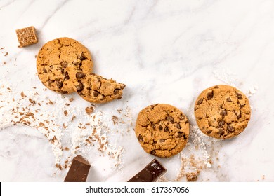 The process of making chocolate chips cookies. Overhead shot of biscuits with chocolate pieces, flour, and cane sugar around them, with a place for text