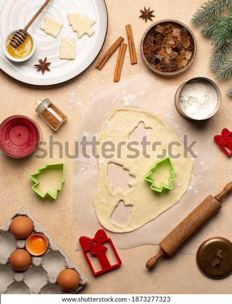 Process of making Christmas cookies with homemade dough,cookie cutters in the shape of tree and gift box,rolling pin,flour,cinnamon,cocoa powder and fresh eggs on beige table.Top view.