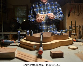 The process of making a classical guitar. Adhering tailblock and neckblock guitars.