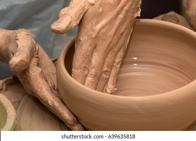 Process of making clay bowl on pottery wheel. Potter at work. Close-up view.