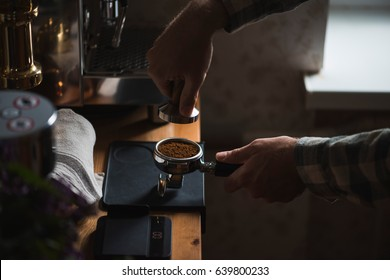 The process of making coffee step by step. Man tamping freshly ground coffee beans in a portafilter on a working wooden table