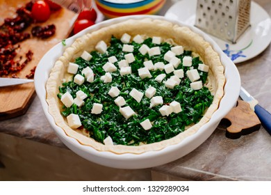 The process of making French quiche. Ingredients pie quiche. French quiche with cheese, spinach, mushrooms, bacon, dried tomatoes. Cooking.