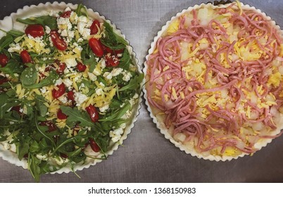 The process of making French quiche. Ingredients pie quiche. French quiche with feta cheese, rocket, cherry tomatoes. Lorraine quiche Cooking. - Image