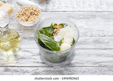 The process of making pesto sauce in a blender from cheese ,pine nuts, olive oil, basil, garlic on the white wooden table