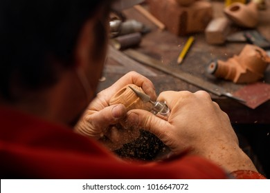 Process of making a pipe. Craftsman is shaping a stummel with a power sanding tool. Handmade goods, woodworking shop.