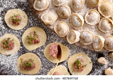 Process of making ravioli, pelmeni or dumplings with meat on wooden table