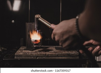 The process of making silver jewellery. Melting raw silver. Female artist hands close up. Crafting a silver ring, see the entire series