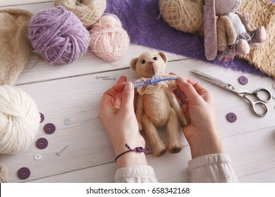 Process of making vintage toy, top view. Artisan pov, needlewoman hands sewing handmade teddy bear, home workshop