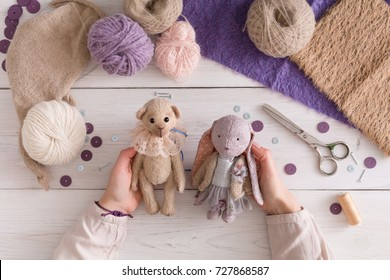 Process of making vintage toy, top view. Artisan pov, needlewoman hands holding handmade teddy bear and rabbit, home workshop