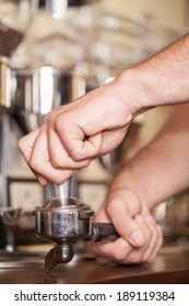 The process to making your coffee. Close up a barista making coffee through the devices of the coffee machine