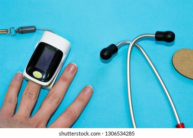 Process of measuring heart rate and oxygen level in blood. Stethospope, oximeter on patient's finger on blue background. Diagnosis and treatment in medicine. Medical composition, flat lay top view
