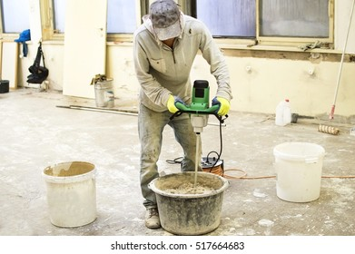 The process of mixing putty mixture for construction on the background reconstruction room