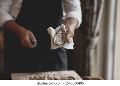 The process of opening oysters, a knife for oysters, male hands open oysters
