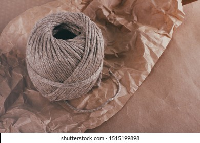 Process of packaging parcels. Pouch wrapped in brown craft paper and tie hemp cord. Crumpled paper texture background. Delivery service. Your order. Online shopping.