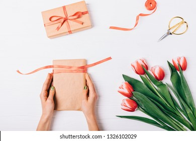 Process of packing gifts for holiday, flat lay. Top view of female's hands holding present box with satin ribbon near pair of scissors and bouquet of red tulips on white wooden table.