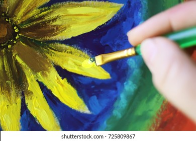 Process of painting by oil paints on canvas. A hand with brush.