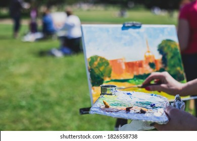 Process of plein air painting, group class of adult talented students in the park with paints easels, and canvases during lesson of watercolour painting outdoors