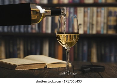 The process of pouring wine into a glass that stands on a wooden table with a book and a magnifying glass on the background of a bookcase