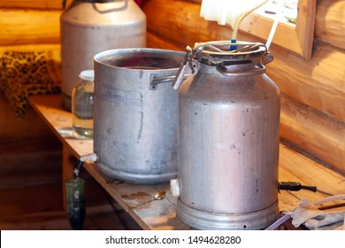 The process of preparing moonshine in a village bath in a primitive moonshine distilling-apparatus. Moonshine. Manufacture of moonshine in Russia.