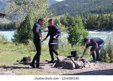 The process of preparing a tourist lunch by young tourists. Sports guys in wetsuits on a halt during rafting on the Katun River, Russia, Altai Republic