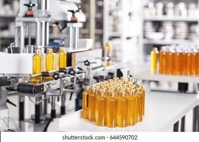 Process of producing cosmetics. Many glass bottles with yellow liquid standing near conveyor on factory. Row line of glass bottles on factory. Innovation and creation concept. Producing new products