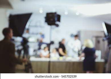 The process of recording a TV program in the culinary studio, blurred background. Video light stands with equipment and crew.
