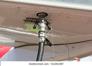 The process of refueling passenger plane close up. Fuel hose inserted in the aircraft wing.