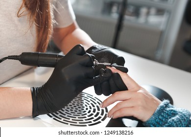 The process of removing nail polish with a milling cutter for a manicure. The manicurist removes the old cover from the nail close up view.
