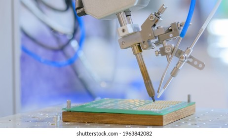 Process of selective soldering components to printed circuit board in demo mode at exhibition - close up view. Automated technology, industrial, electronic, production, manufacturing concept