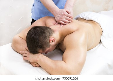 The process of sports massage is done by a man in a massage salon
