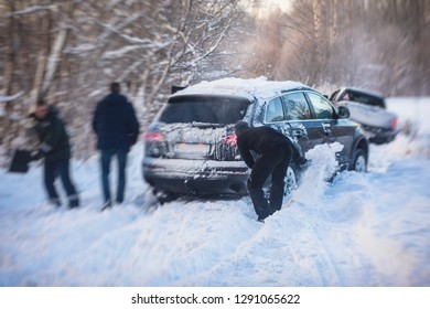 Process of taking out suv car stuck in snow, men digging and pushing the car out of snow, concept of winter problems with car