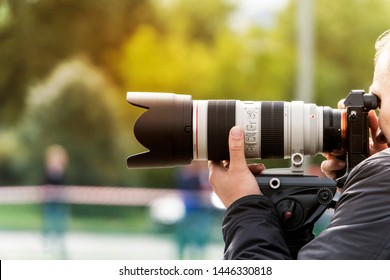 Process of taking pictures outdoors. Professional photographer zooms to make a shot. Man shoots with a modern lens outdoors. Shooting with lens. Paparazzi with high-end objective. Photographic skill