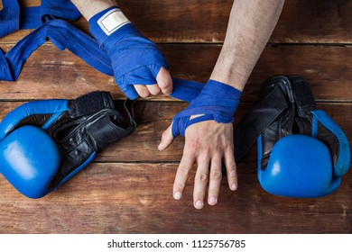 Process of taping male hands before of a boxing match on a wooden background. Boxing gloves lie on the table. Concept of boxing is learning or fighting. Flat lay, top view.