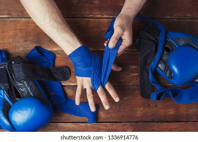 Process of taping male hands before of a boxing match on a wooden background. Boxing gloves lie on the table. Concept of boxing is learning or fighting. Flat lay, top view