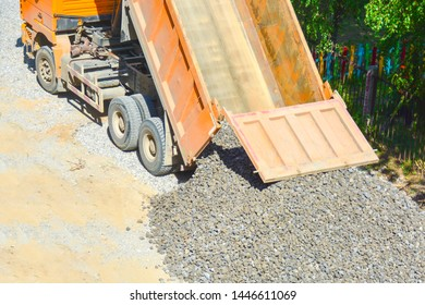 The process of unloading a dump truck, dump truck unloads rubble on the ground, top view. The concept of road construction, construction, shipping, road repairs.