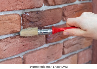 Process of varnishing grout between gypsum decorative bricks. Covering a brick wall with waterproofing coating.