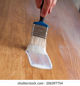Process of varnishing a wooden surface. Closeup.