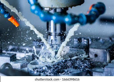 a process of vertical cnc steel milling with external water coolant streams, splashes and a lot of metal chips - close-up with selective focus