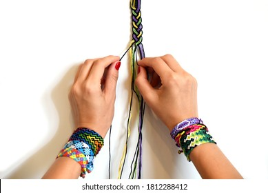 Process of weaving knot for DIY friendship bracelet Pigtail. Female hands with many handmade bracelets on wrists. step by step. White background with copy space