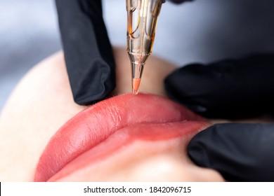 Process woman applying permanent tattoo makeup on lips in beautician salon.
