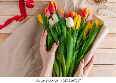The process of wrapping bouquet of fresh tulips in eco-friendly craft paper. Step 1. Gift for spring holiday. Flower business.