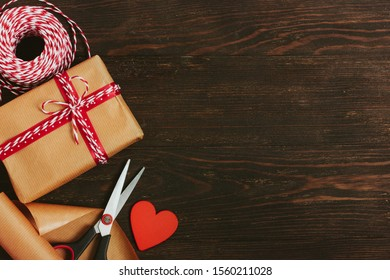 The process of wrapping a Christmas or New Year present. Wrapping paper, gift, cord in a skein, scissors, heart on a dark wooden background. View from above. Place for text