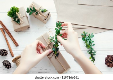 Process of wrapping modern Christmas presents with natural decorations on white background. Gifts boxes in craft paper with twine and green branches. Happy holidays concept. Top view. Flat lay.