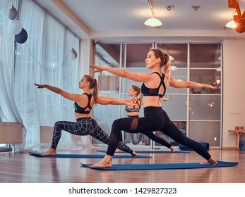 Process of yoga exercises with three beautiful young girls at gymnastic studio.