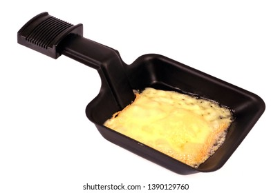 Processed cheese in a raclette pan on a white background