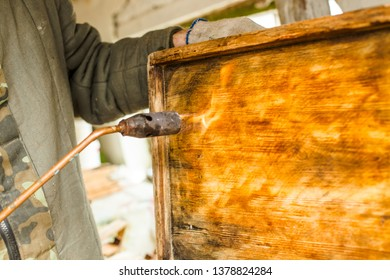 Processing of bee frames and hives for the honey harvest season. Firing the wooden parts of the hive with a blowtorch. Beekeeping work in the spring and after winter.