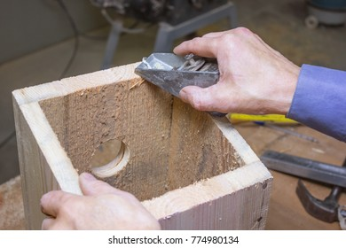 Processing of details of a wooden birdhouse in the workshop