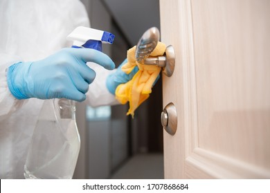 Processing disinfection of apartment premises from coronavirus and bacteria, cleaning company cleans doorknob virus.