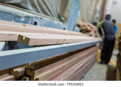 Processing of wooden beams by workers